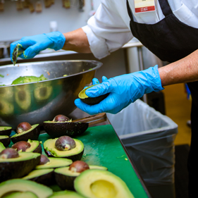 Halved avocados being added to a bowl by an employee with a black apron and blue gloves.