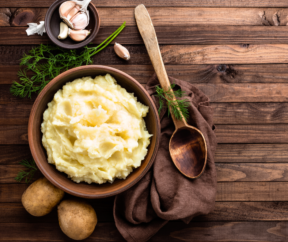 Mashed Potatoes in a Bowl. Cloves of garlic, greens, and uncooked potatoes as decoration on the side with a wooden serving spoon.