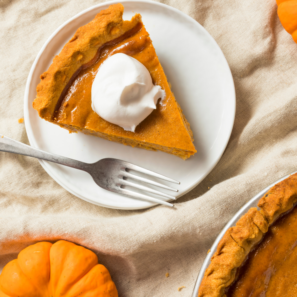 Pumpkin pie with a dollop of whipped cream