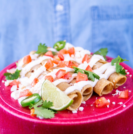 A red plate with taquitos topped with dairy free sour cream, tomatoes and cilantro with a lime wedge on the side
